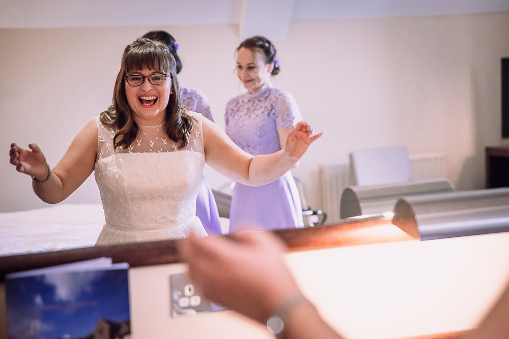 The bride looks excited as she looks at her reflection in the mirror, her arms are up to the side and she is laughing