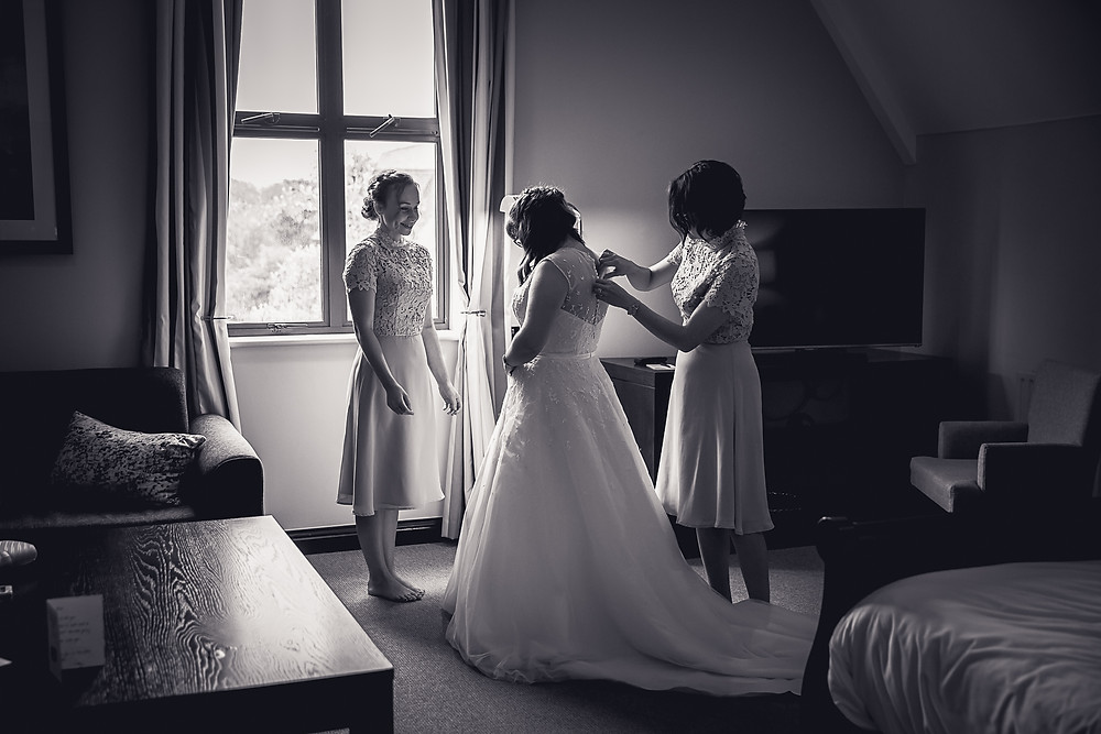 A bride and her bridesmaid stand in a hotel room. One of the bridesmaid is doing up the bride's dress