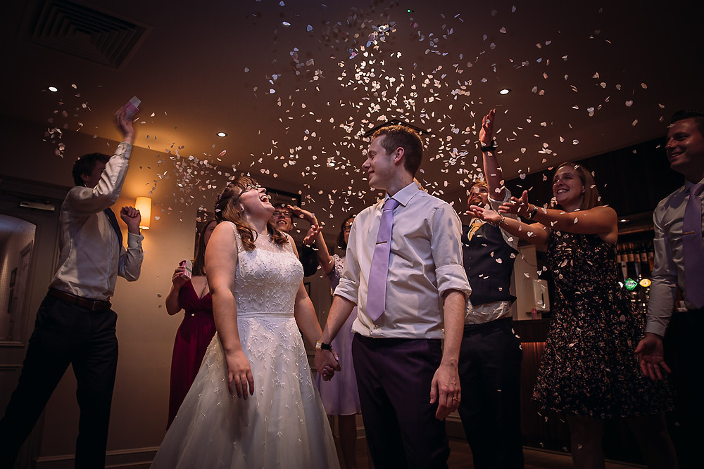 The bride and groom laugh as confetti falls around them