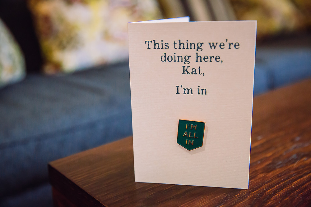 A card is on a table with the words 'This thing we're doing here, Kat, I'm all in'. There is also a badge with the words 'I'm all in'