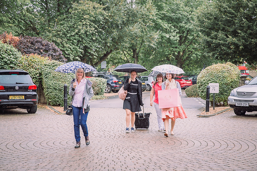Four women walk into a hotel in the rain, each holds an umbrella