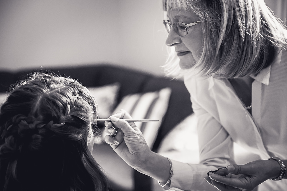 The mother of the bride applies eye shadow to the bride using a brush