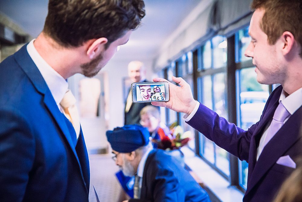 the groom and a guest have a video call on a mobile phone with a friend who cannot be present