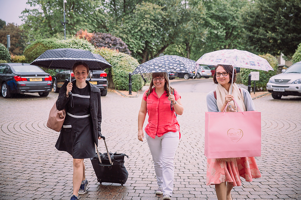 Three women walking into a hotel in the rain, each holding an umbrella. - Oxford wedding photography
