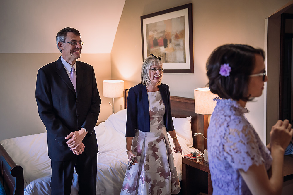 The bride's parents look happy and excited in a hotel room
