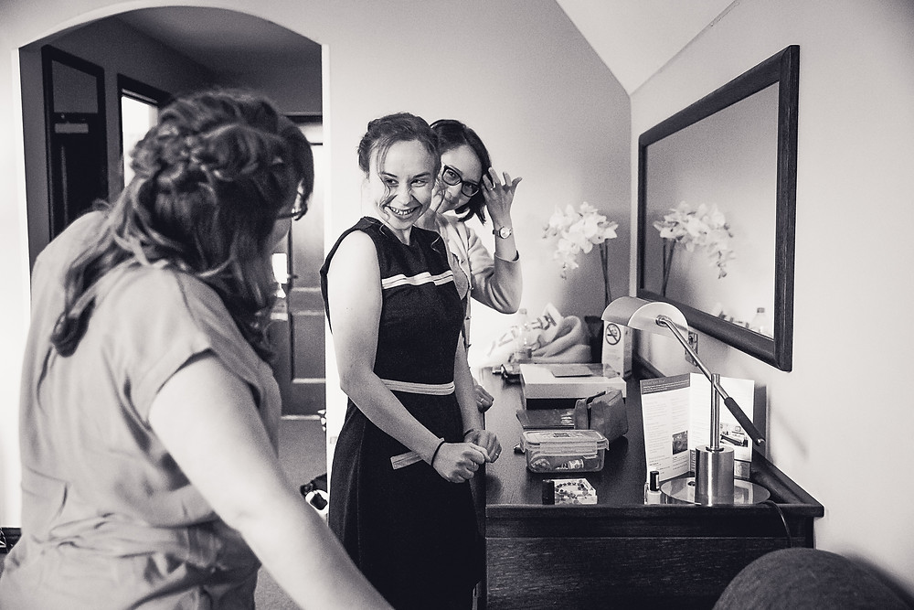 A bride and her bridesmaid get ready together and look excited. The image is in black and white