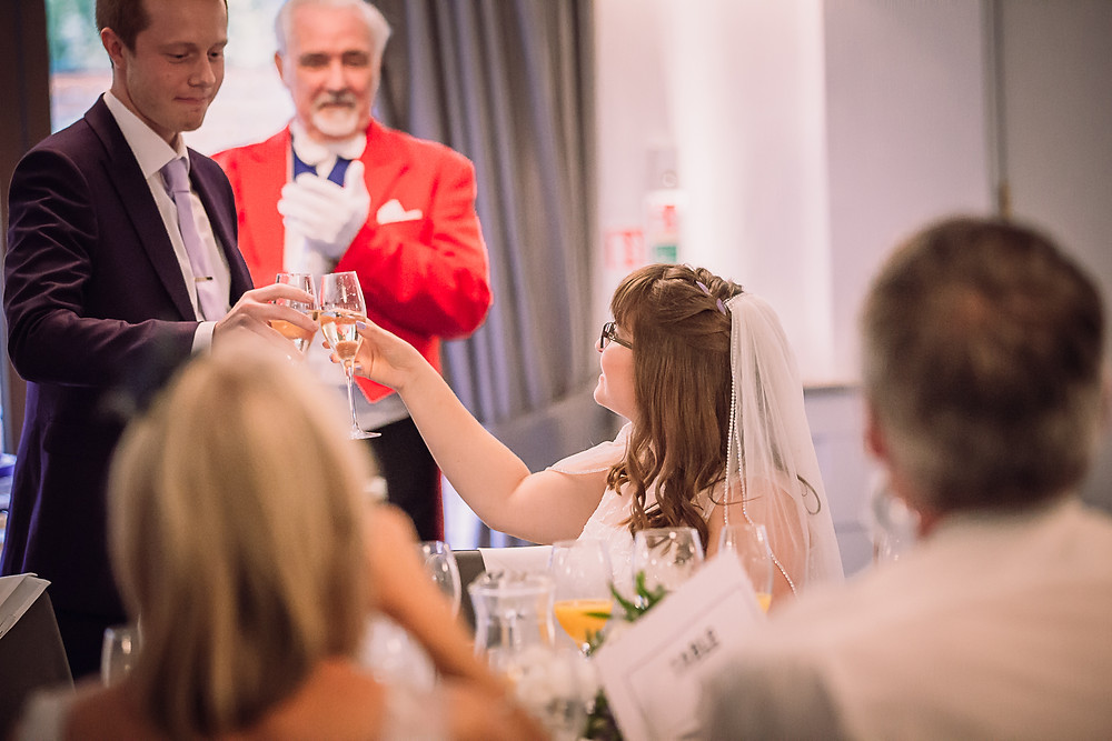The bride and groom toast their glasses