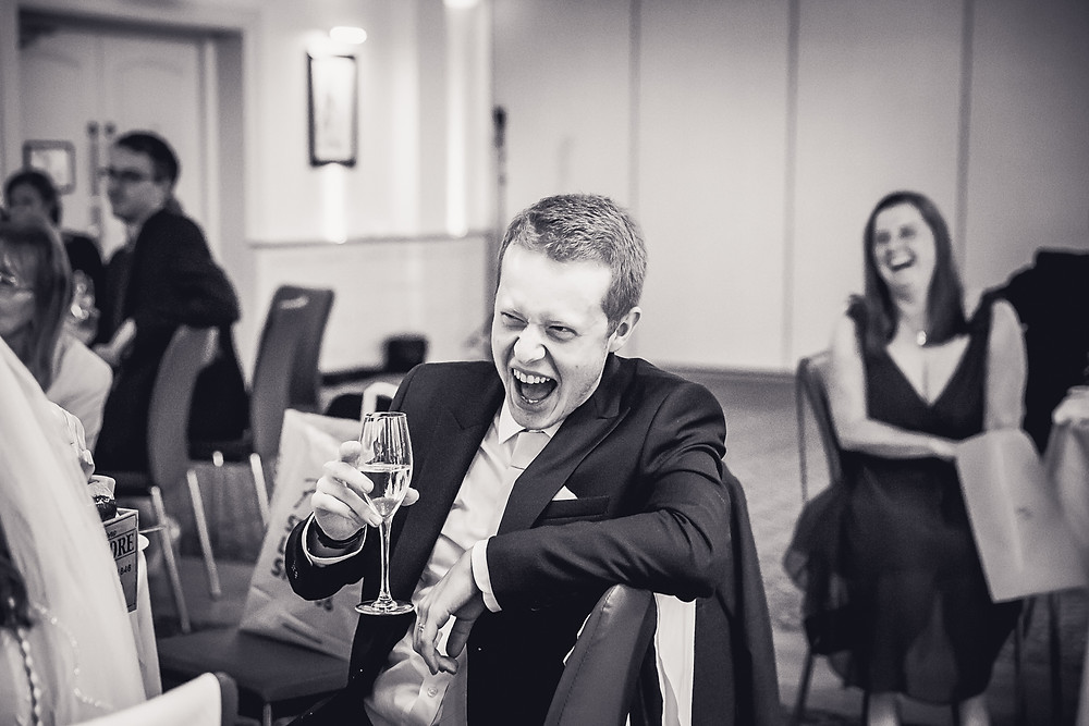 the groom laughs and toasts as a speech is made