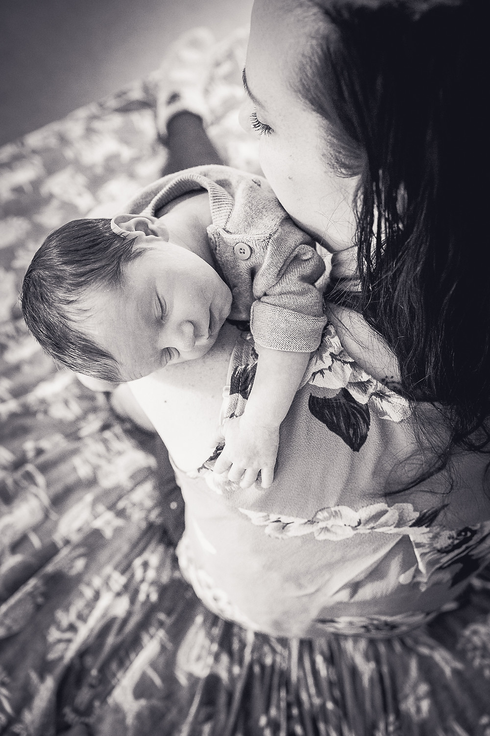 A back and white photography of a women holding her baby over her shoulder, the baby is asleep