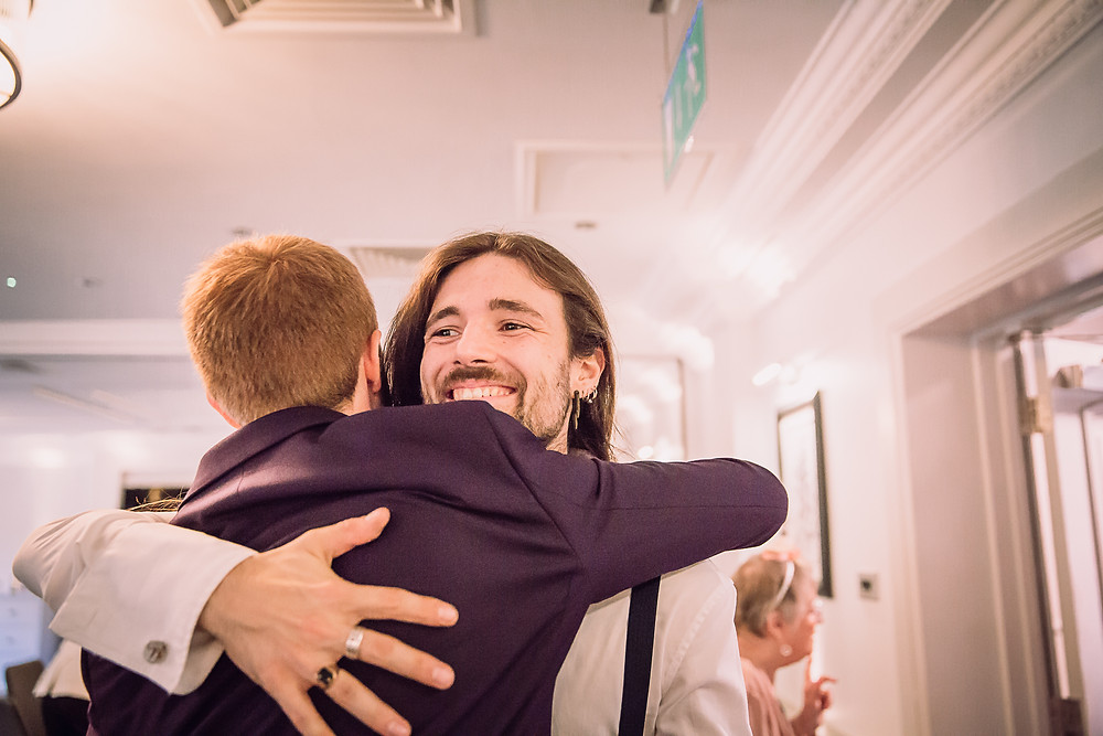 A guest looks happy as he hugs the groom