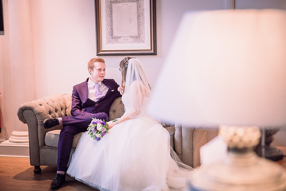 The bride and groom sit and talk on a sofa. The groom wears a purple suit