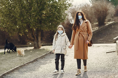 mother-with-daughter-in-face-masks-walki