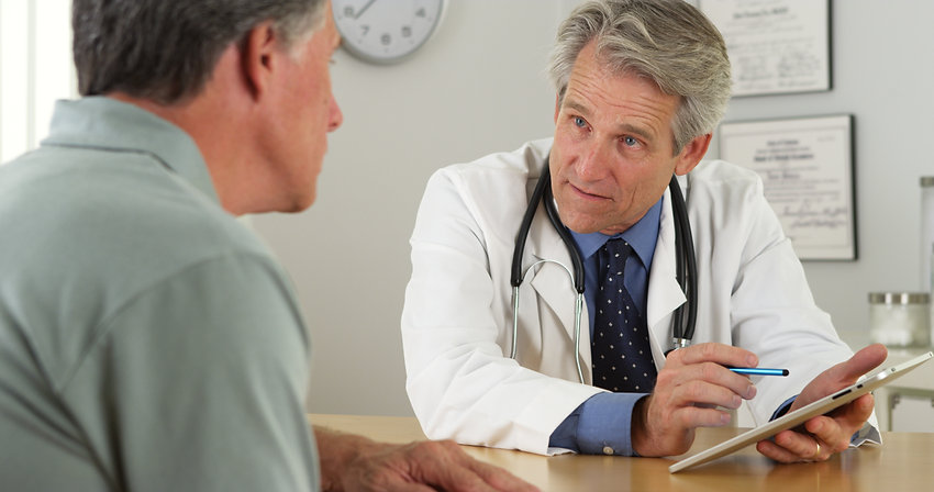 Mature doctor talking with patient and t