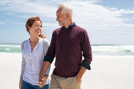 Happy senior couple walking on the beach