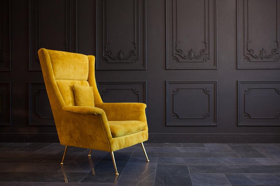 Stylish bright yellow chair against a da