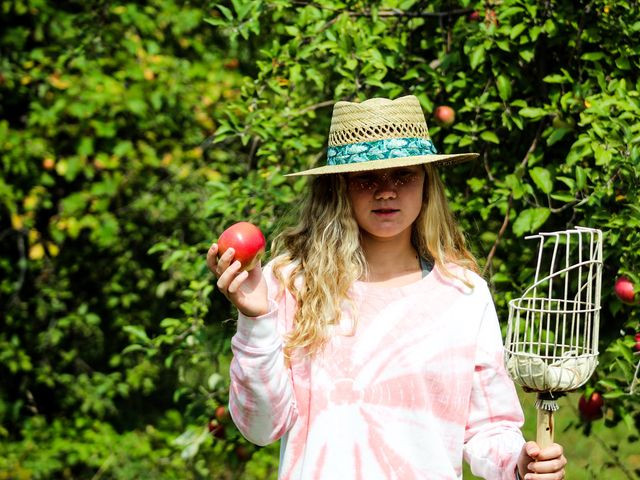Girl poses with apple and picking pole