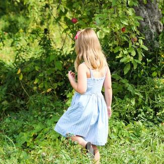 Girl walks through orchard