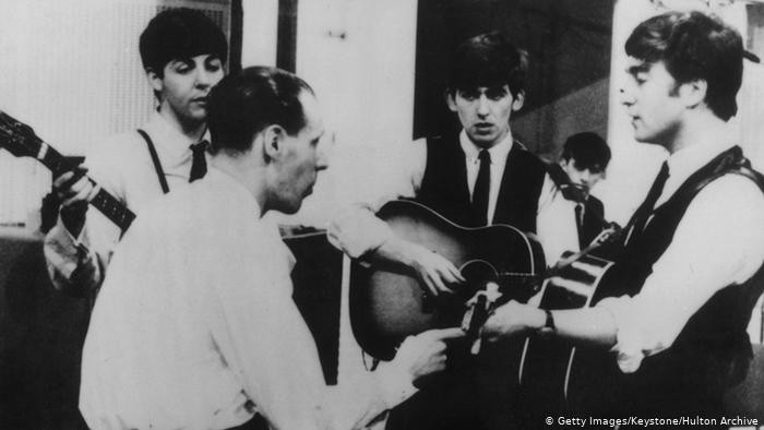 George Martin and The Beatles all together at a performance mingling with each other.