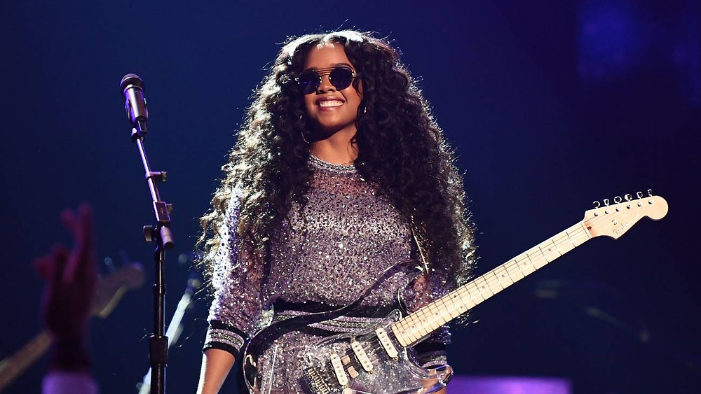 H.E.R. at the Grammy's with her shades and guitar.