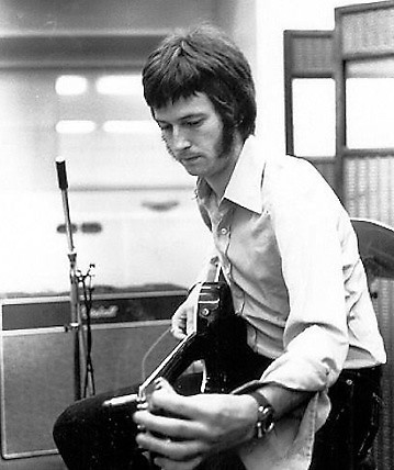 Eric Clapton in a black and white picture playing a guitar