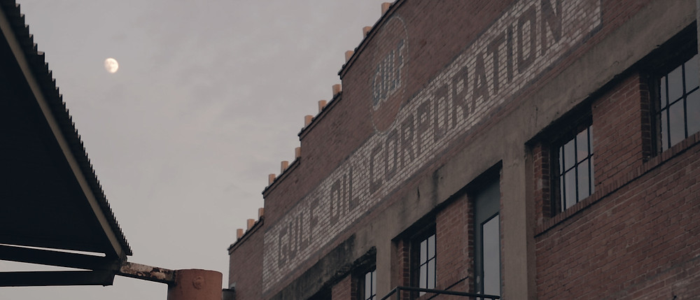 "Side of the Hickory Street Annex Building B with an old factory marking saying "" Gulf Oil Corporation""."