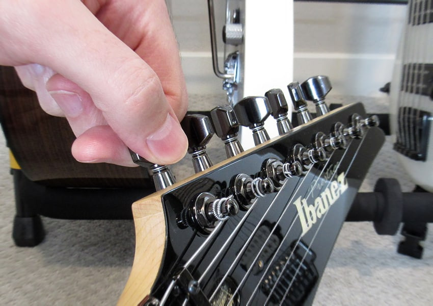 A hand tuning the pegs of a guitar