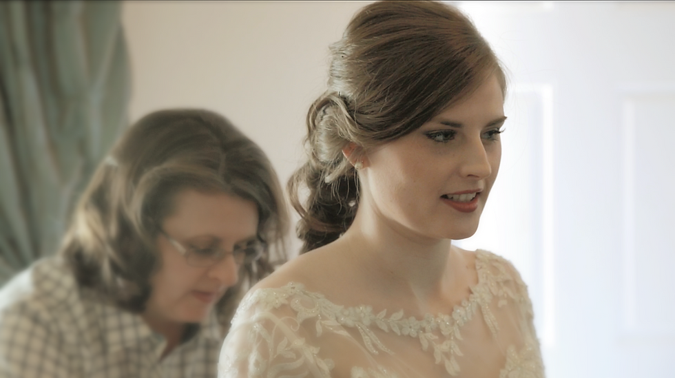 A wedding bride getting her dress buttoned up by her beloved mother on her wedding day.