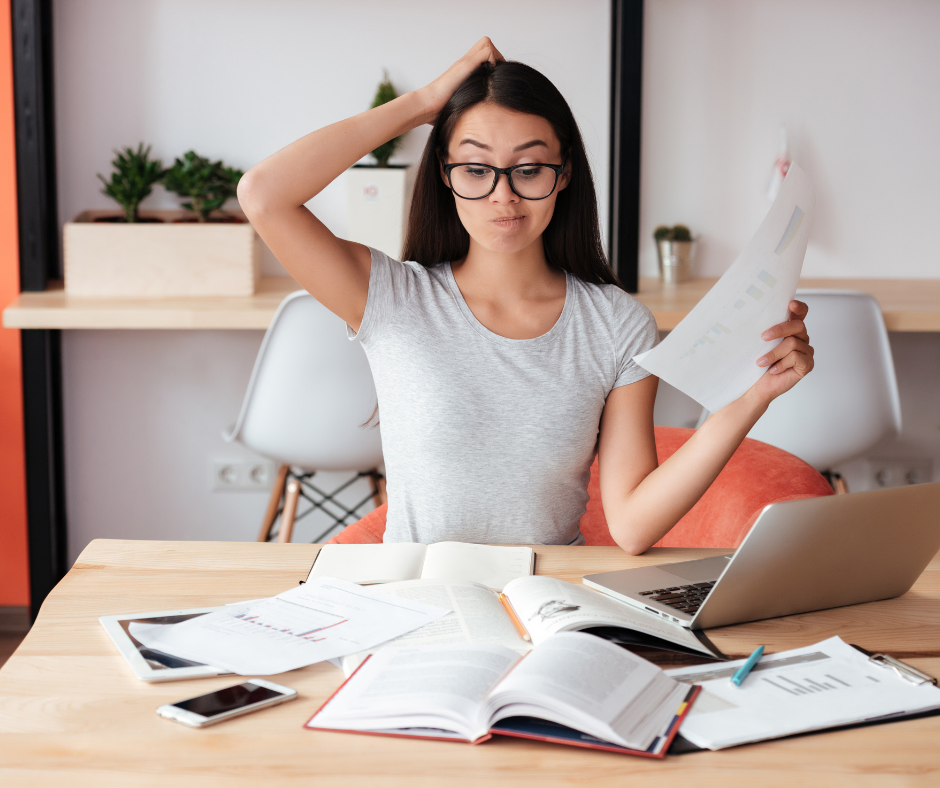 woman disorganized with paperwork and laptop