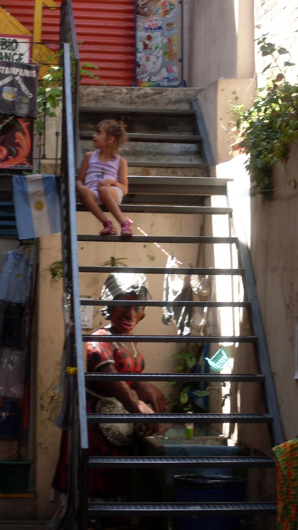Little girl sitting on stairs in La Boca
