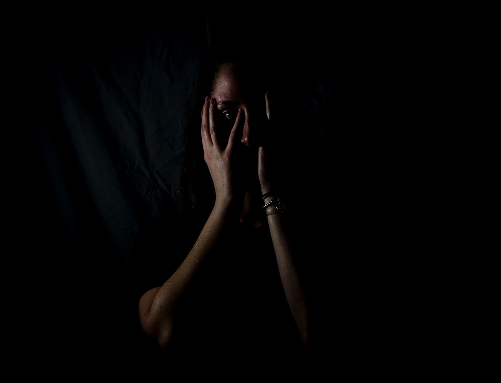 A shadowy photo of a woman holding her hands to her face.