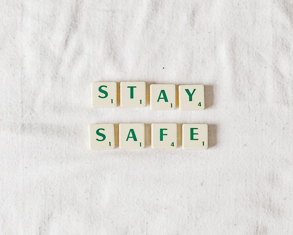 Cream scrabble tiles with green lettering spelling out 'stay safe'.