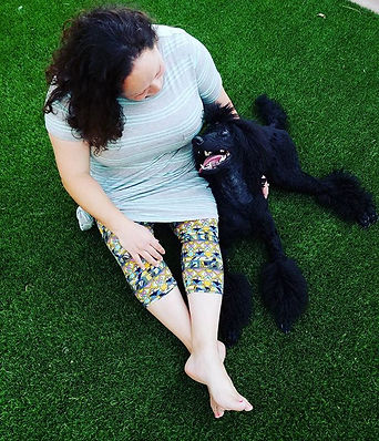 woman with dark shoulder length hair sits on the green grass with her black poodle
