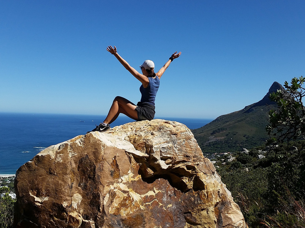 une femme assise sur un rocher les bras en l'air