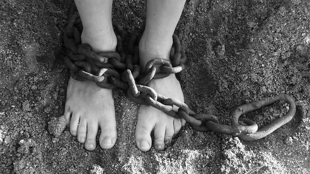 deux pieds enchaînés par une lourde chaîne