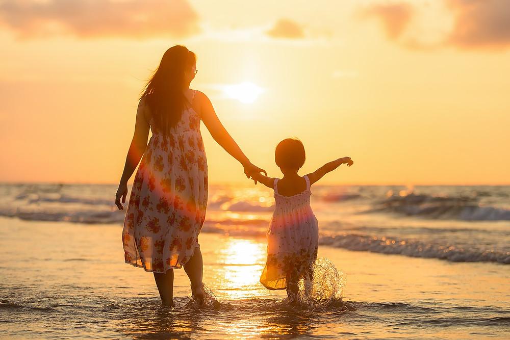 Une maman et son enfant de dos face à la mer