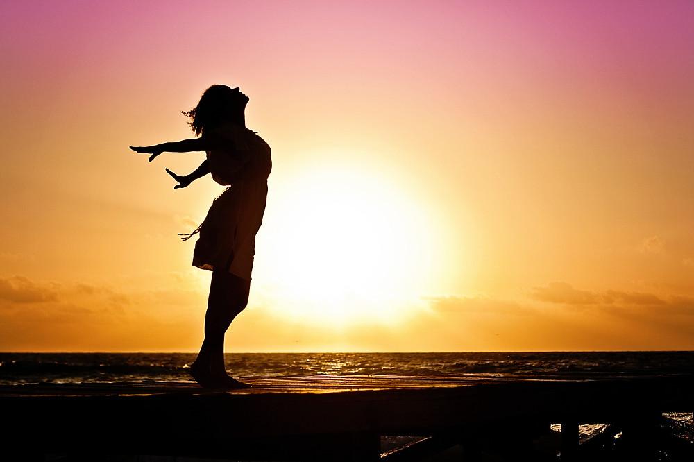 femme et coucher de soleil sur une plage