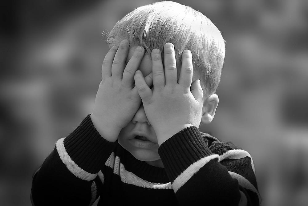 enfant qui masque ses yeux avec son visage