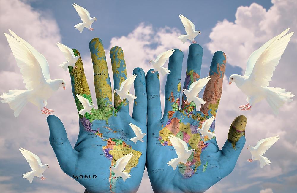 monde peint sur deux mains avec des colombes blanches