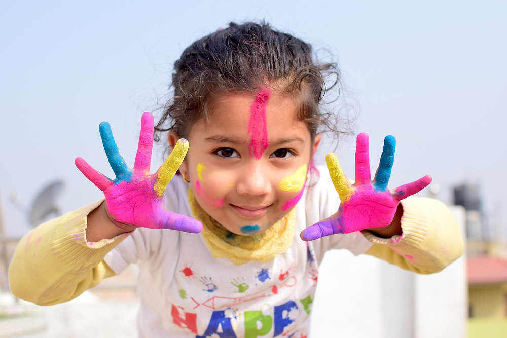 petite fille ayant de la peinture sur les mains et le visage