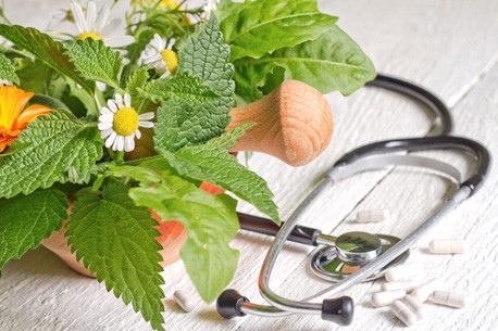 Stethoscope & fresh herbs representing integrative medicine, which combines conventional and alternative therapies