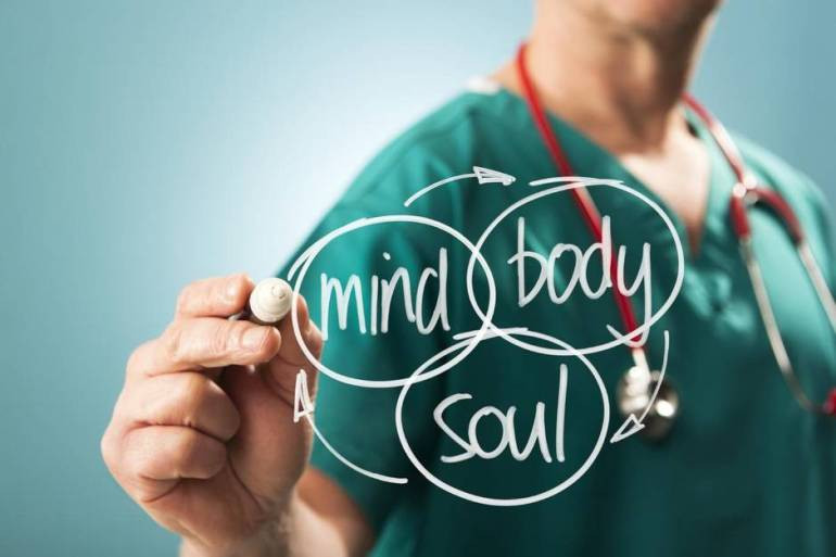 An image of a medical practitioner writing mind, body, soul with arrows linking them to represent integrative medicine