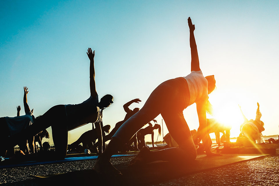 Silhouette of people doing yoga outdoor