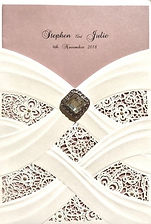 A vintage white lace wedding invitation - laser cut pocket. This features a pink strip and a heart embellishment, and the invitation insert is printed on a metallic pink paper that sits behind the lace pocket creating a beautiful contrasting background.  Handmade by Jules.