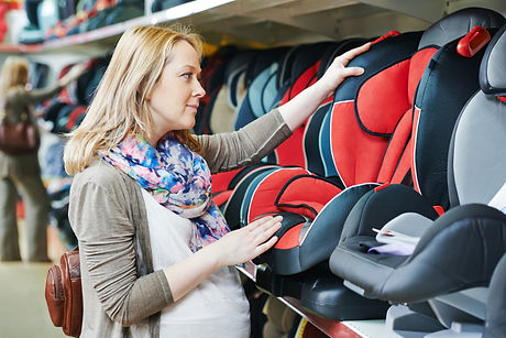 woman choosing child car seat for newbor