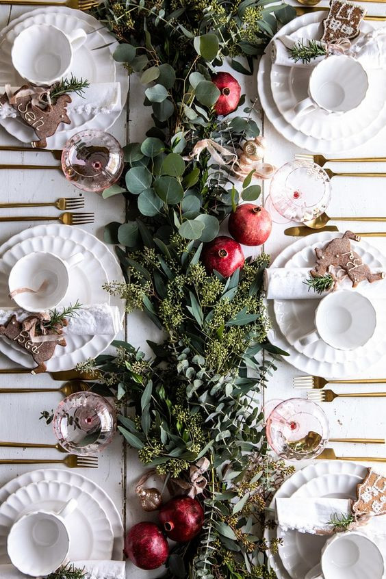 elegant Christmas table decorations using seasonal fruit and white classic plates with red tree decorations