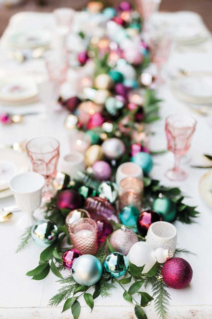 Colourful Christmas table decorations using repurposed Christmas baubles with greenery