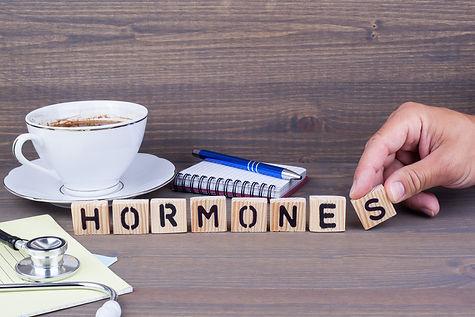 hormones. Wooden letters on dark backgro