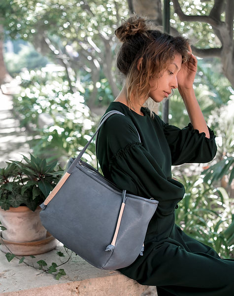 maravillas bags, buy eco leather bags from Spain, vegetable tanned, sustainable bags handmade and fair produced, blue bag, woman, green dres, naure, garden, mediterranean, soft light.