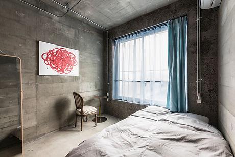 コンクリート壁のベッドルーム