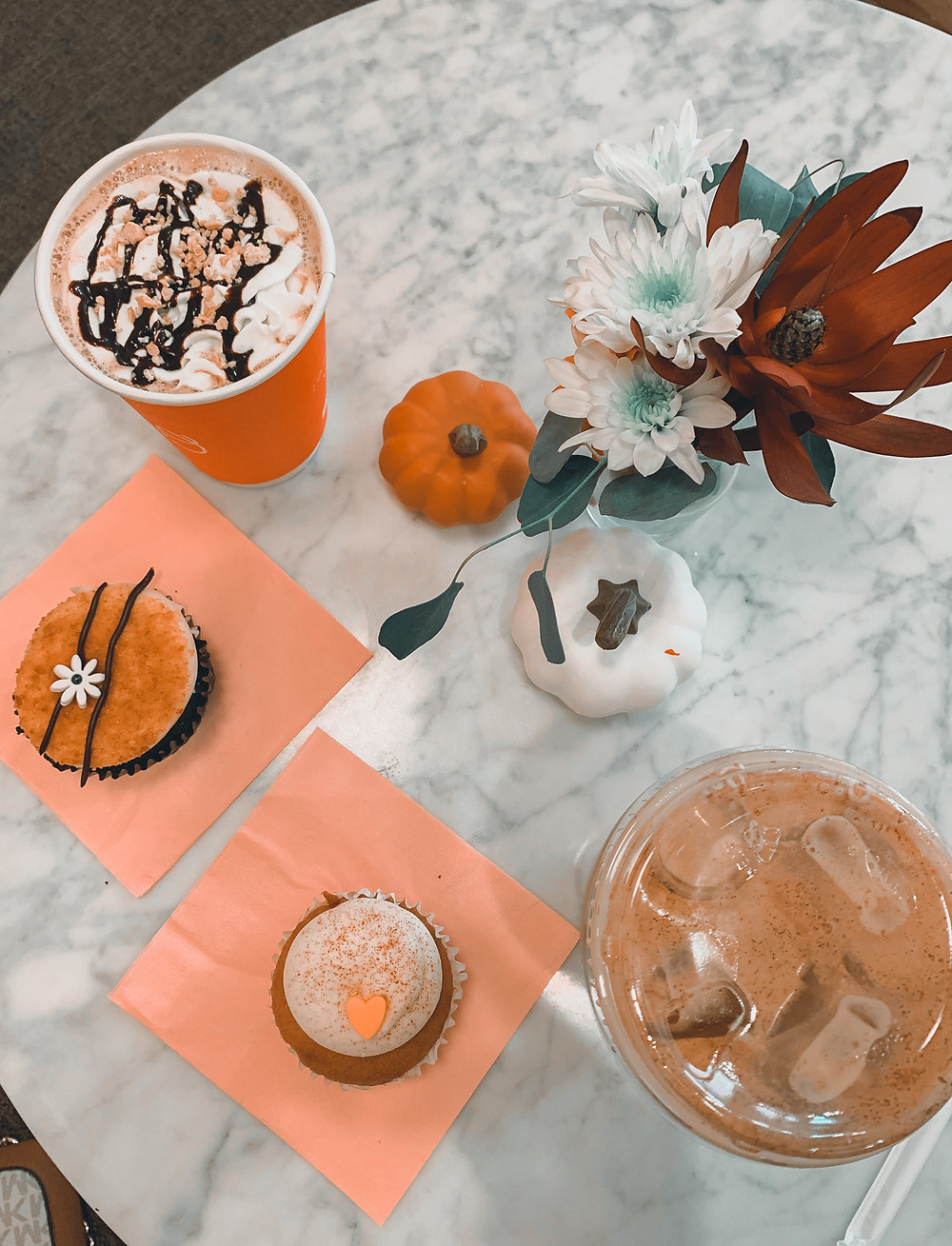 Lancaster Cupcake, coffees, s'mores latte, iced pumpkin spice latter, mini pumpkins, flowers in small vase, pink napkins, cupcakes